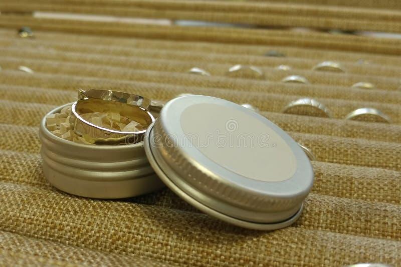Deux anneaux d'or blanc sont dans une boîte ronde en métal Dans la perspective des palettes d'autres bijoux image libre de droits