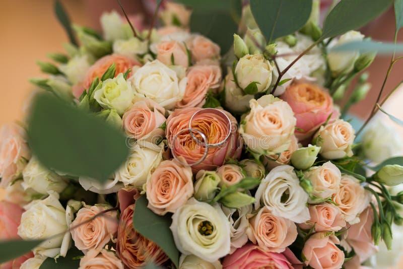 Deux anneaux d'or les épousant se trouvant sur des bouquets d'un mariage avec les roses oranges et beiges photos libres de droits