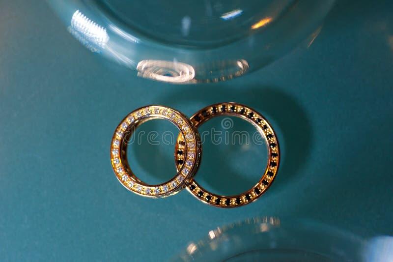 Deux anneaux d'or sur le fond de scintillement de turquoise image stock