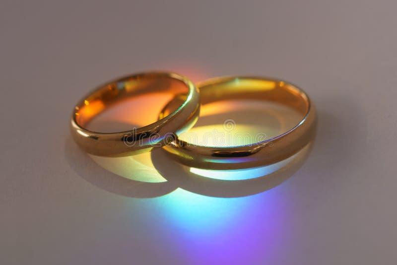 Deux anneaux de mariage avec la lumière d'arc-en-ciel images stock