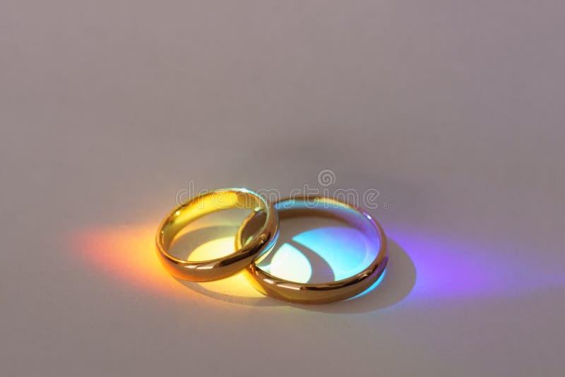 Deux anneaux de mariage avec la lumière d'arc-en-ciel photos stock