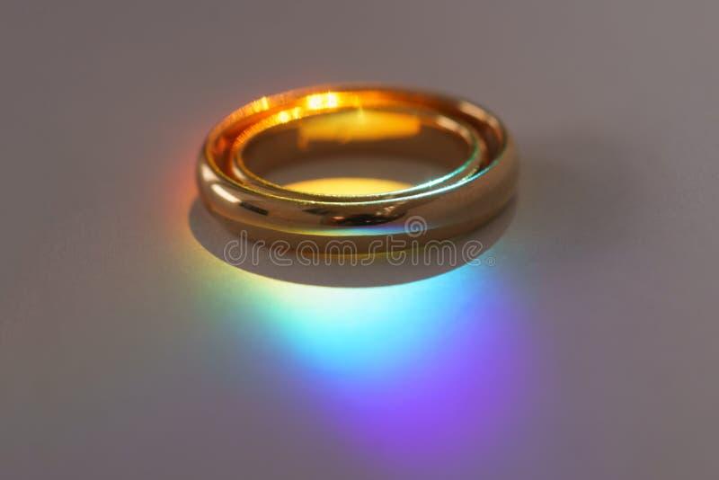 Deux anneaux de mariage avec la lumière d'arc-en-ciel images libres de droits
