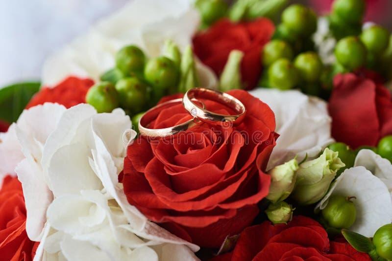 Deux anneaux de mariage sur le bouquet coloré des roses blanches et rouges, fin  photographie stock libre de droits