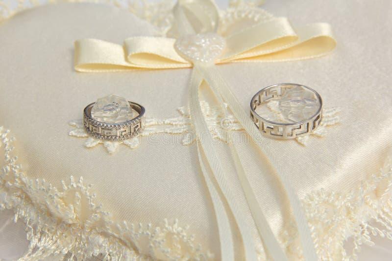 Deux anneaux de mariage sur un coussin photographie stock libre de droits