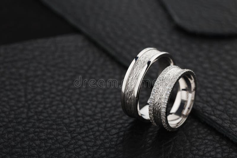 Deux anneaux de noces d'argent sur le fond en cuir noir photo libre de droits