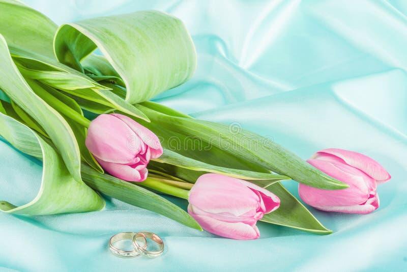 Deux anneaux et tulipes sur une turquoise image libre de droits