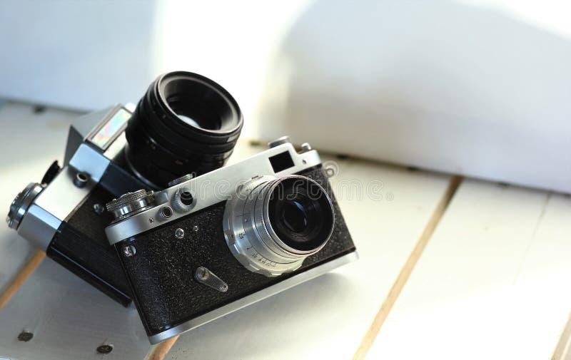 Deux appareils-photo noirs de photo de vintage de vieux-école sur les planches en bois blanches, intérieur ensoleillé photographie stock