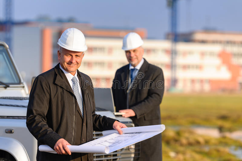 Deux architectes aux plans de revue de chantier de construction image stock