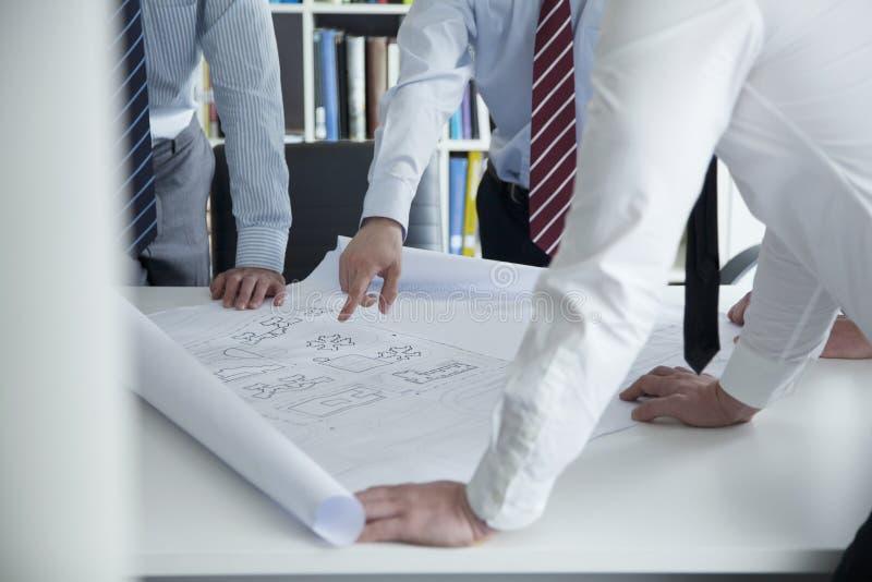 Deux architectes discutant au-dessus d'un modèle dans le bureau, mi section images stock
