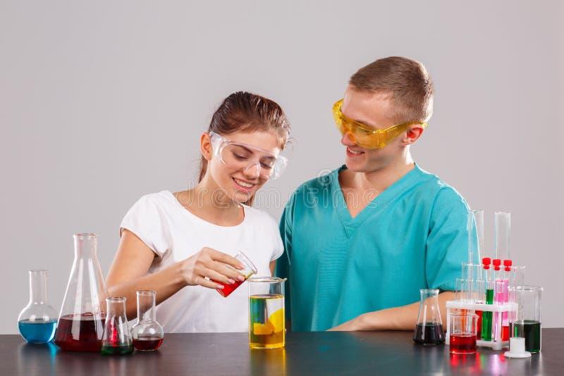 Deux assistants, la fille verse un liquide rouge d'un verre dans un verre avec le liquide orange images libres de droits