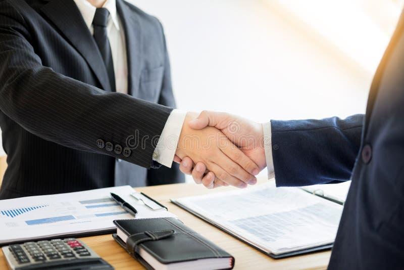 Deux associés d'hommes d'affaires se serrant la main au cours d'une réunion pour s'occuper photo stock
