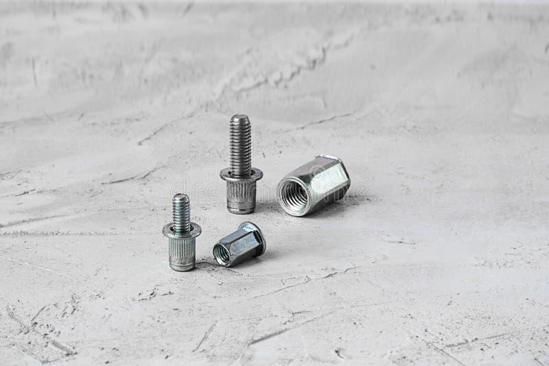 Deux attaches de rivet de bruit en métal de taille différente, sur le fond gris de ciment Horizontal avec l'espace de copie pour  photographie stock libre de droits