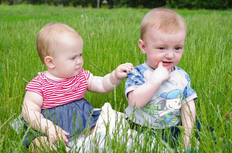 Deux bébés dans l'herbe photo stock