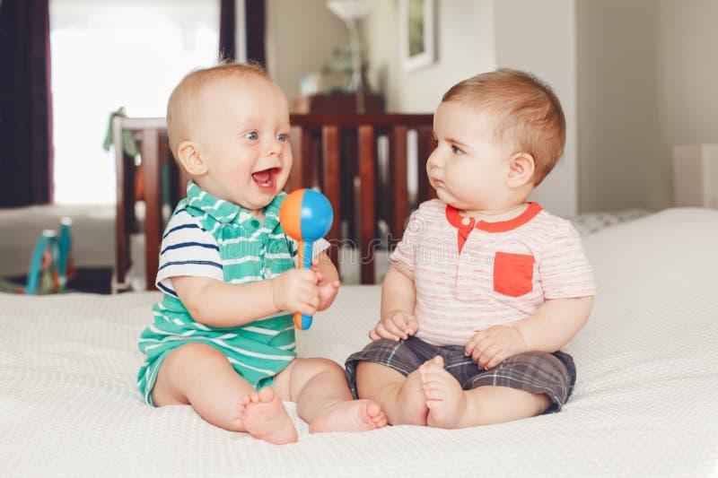 Deux bébés garçon drôles adorables mignons caucasiens blancs se trouvant ensemble sur le lit partageant le jouet image libre de droits