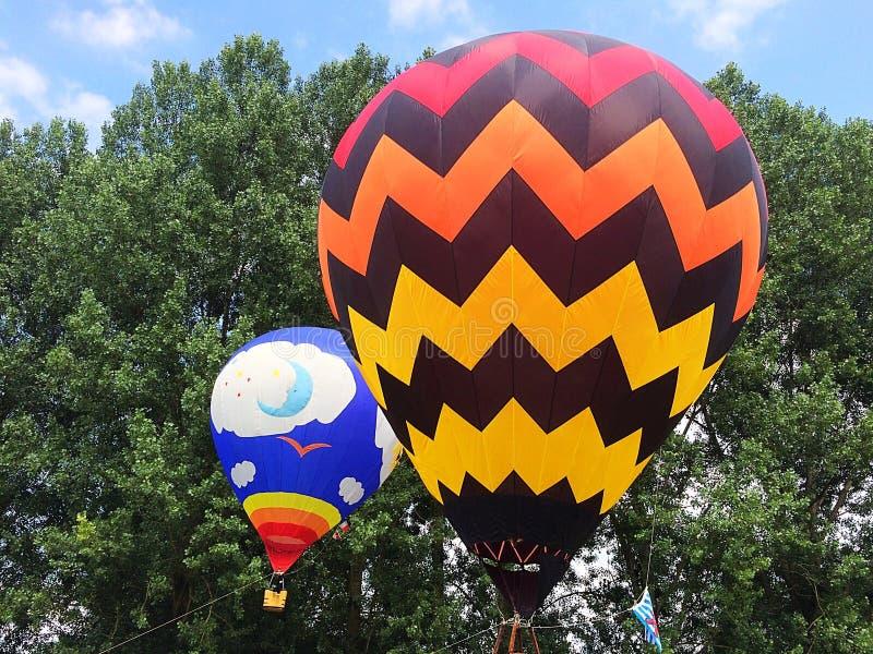 Deux ballons à air chauds devant des arbres pendant le jour s'allument photo stock