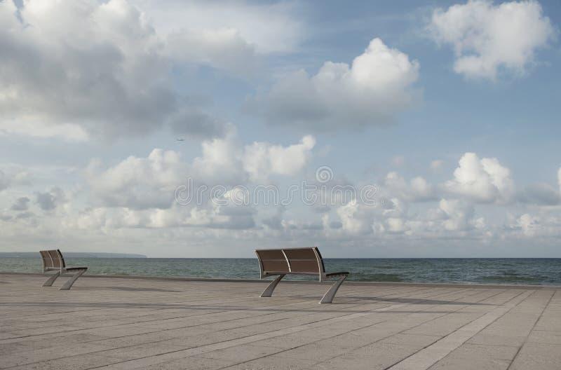 Deux bancs vides par la mer images stock