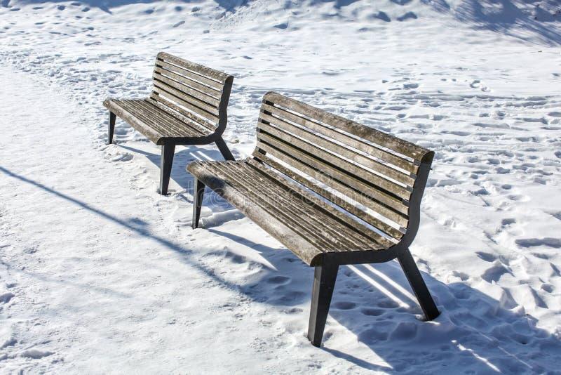 Deux bancs vides sur la neige couverte images stock