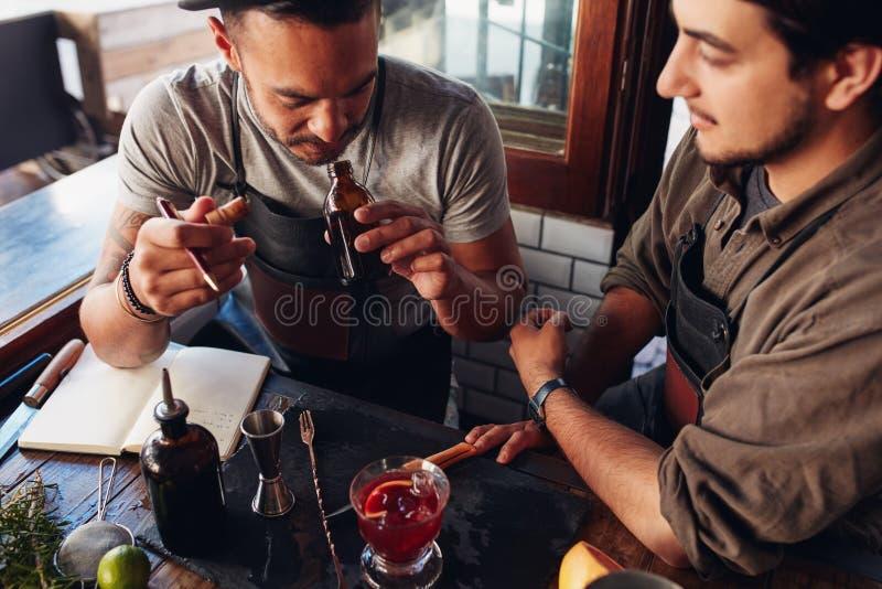 Deux barmans expérimentant avec créer des cocktails photo stock