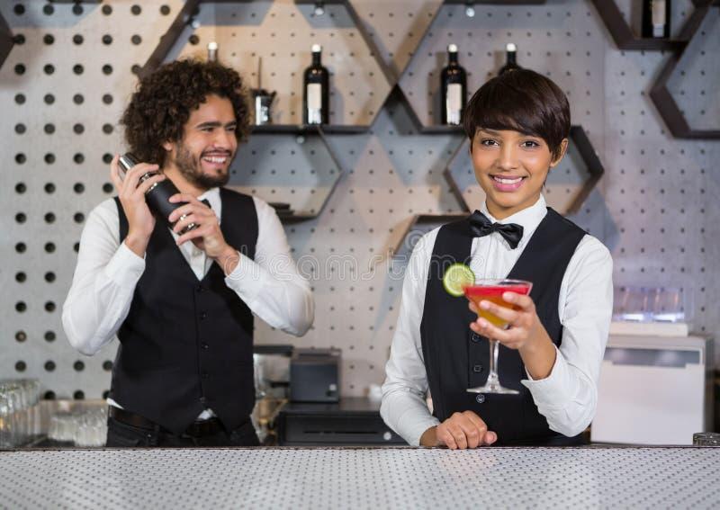 Deux barmans préparant le cocktail et servant dans le compteur de barre images libres de droits