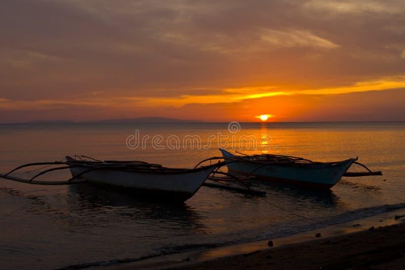 Deux bateaux de Banca au coucher du soleil sur la plage photographie stock libre de droits