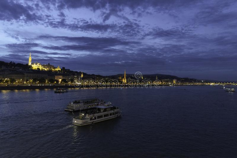 Deux bateaux se déplacent loin sur le Danube pendant qu'il traverse Budapest avec la bastion des pêcheurs et le rivage lumineux image stock