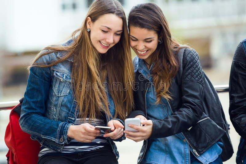 Deux beaux étudiants à l'aide du téléphone portable dans la rue image stock