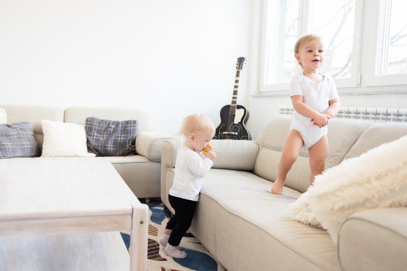 Deux beaux bébés jouant dans le salon blanc de soeur d'isolement par frère de fond images libres de droits