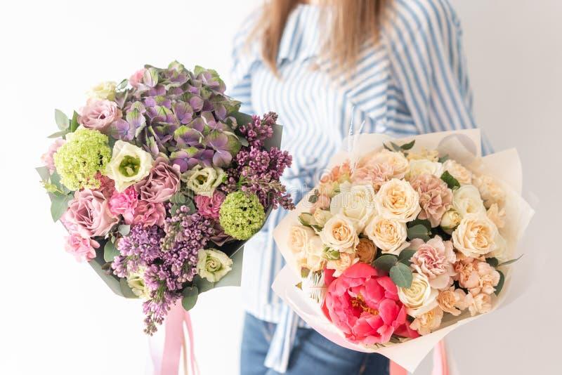Deux beaux bouquets des fleurs m?lang?es chez les mains de la femme le travail du fleuriste ? un fleuriste Couleur en pastel sens photos libres de droits