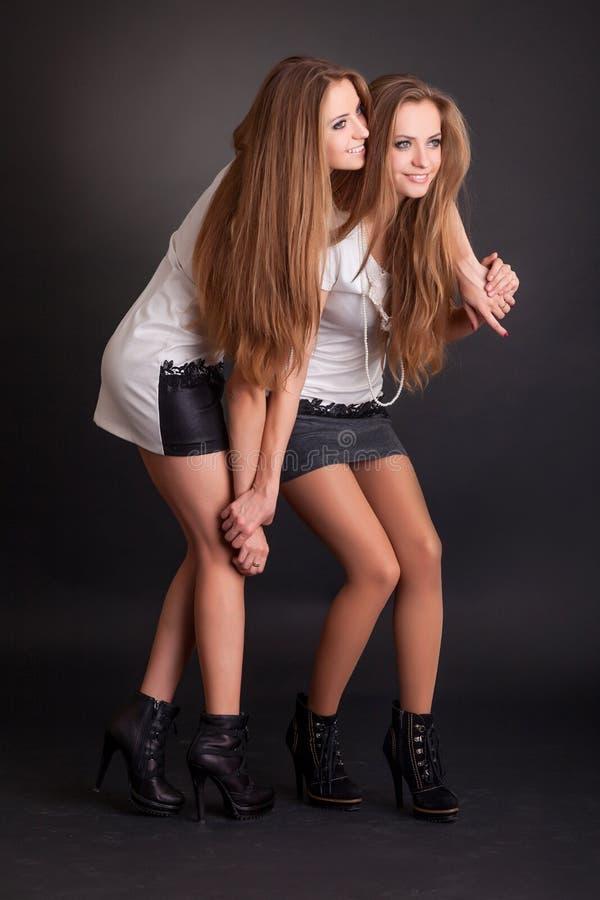 Deux beaux jumeaux de filles, d'isolement sur le noir photographie stock