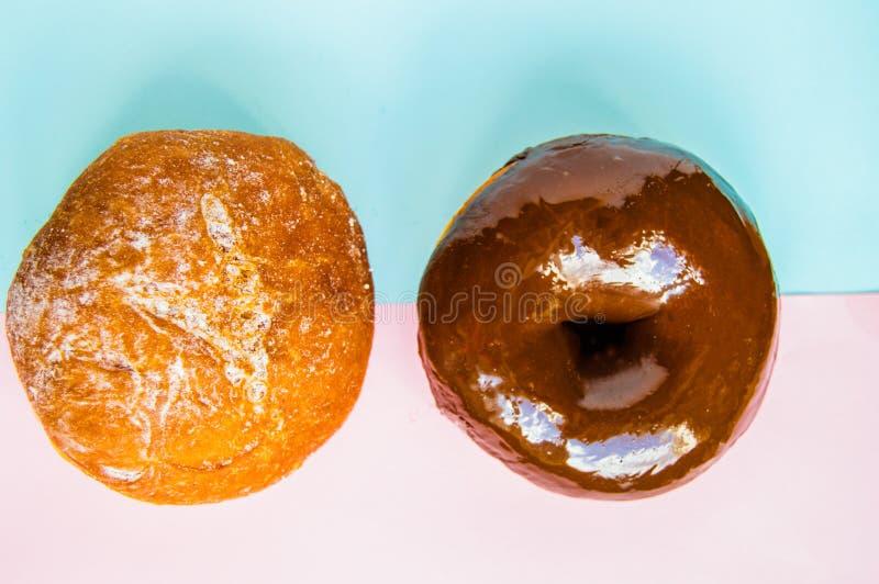 Deux beignets avec le glaçage de sucre en poudre et de chocolat sur le fond rose et bleu en pastel, la vue supérieure, le Flatlay photo stock