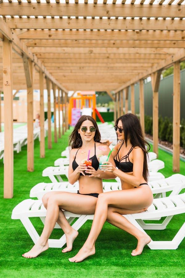 Deux belles femmes appréciant leurs vacances d'été avec des cocktails par la piscine Été image stock