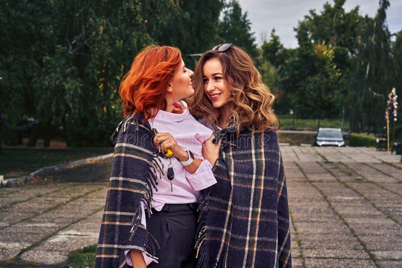 Deux belles femmes avec les cheveux rouges et bruns avec émotion communiquer image libre de droits