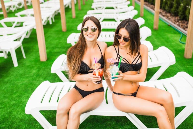 Deux belles femmes ayant des cocktails ensemble par la piscine Été photographie stock libre de droits