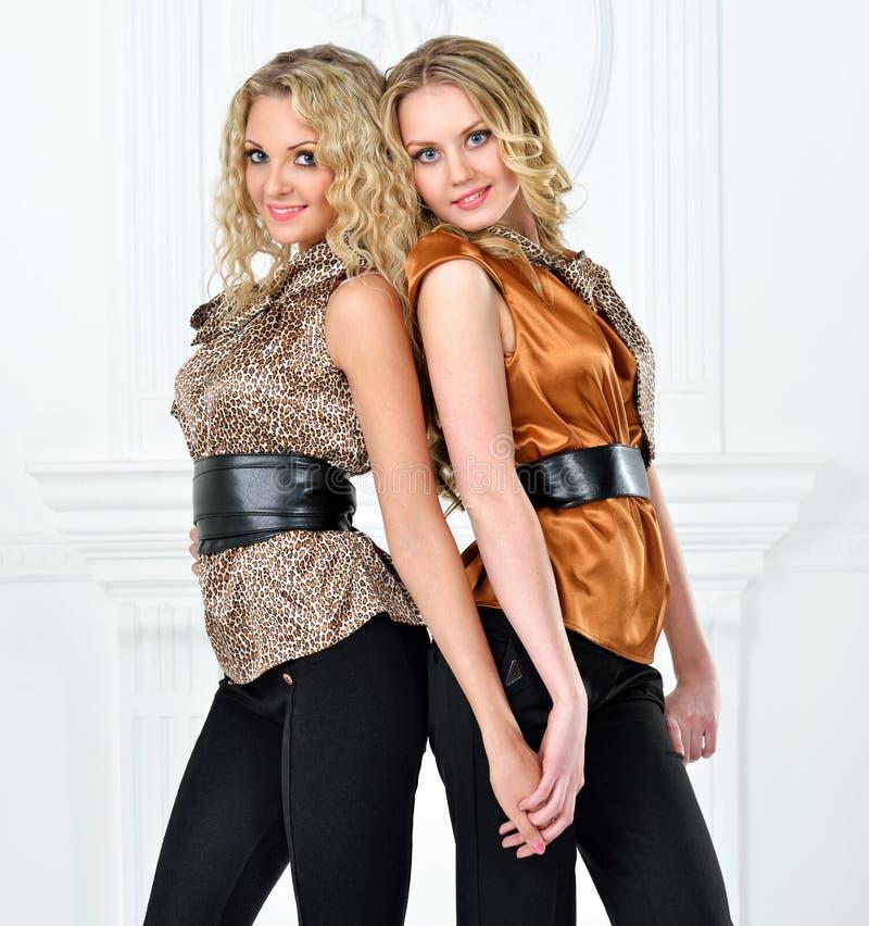 Deux belles femmes dans le costume élégant de soirée. image libre de droits