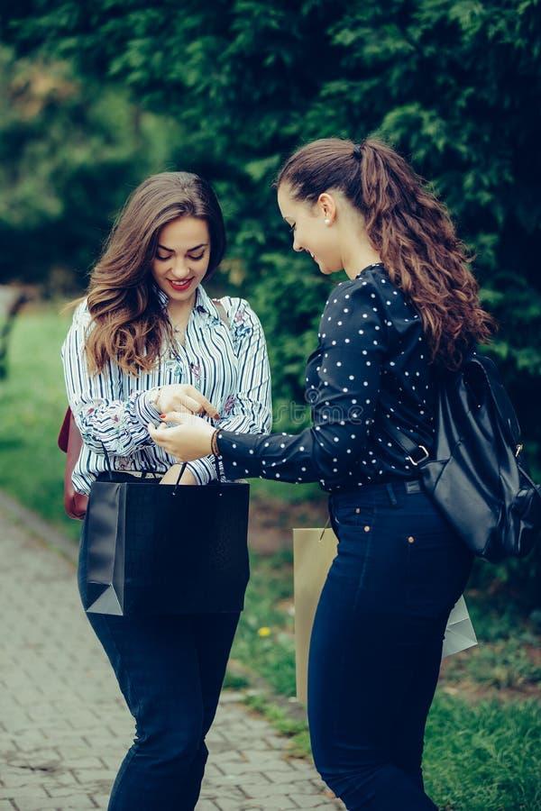 Deux belles femmes marchant en parc apr?s avoir fait des emplettes et avoir partag? leurs nouveaux achats les uns avec les autres photographie stock