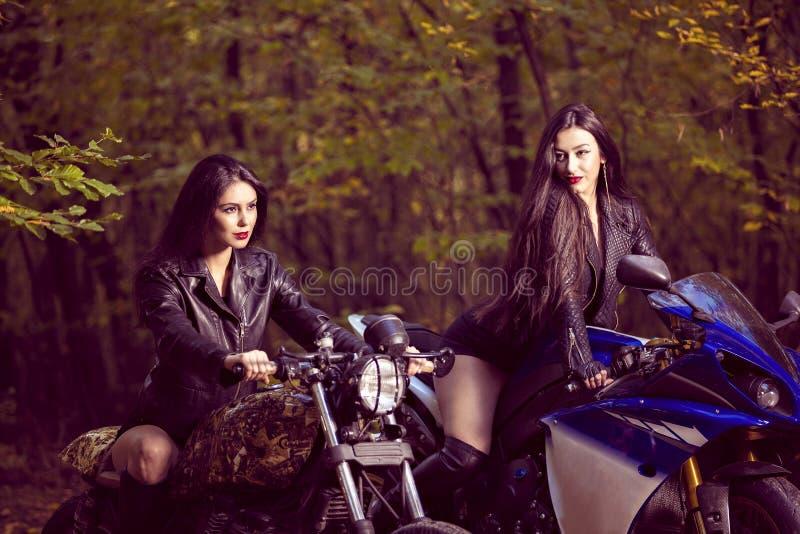 Deux belles femmes passionnées au sujet des motos photos libres de droits