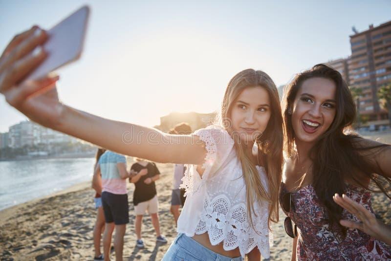 Deux belles femmes prenant le selfie sur la plage ayant l'amusement photographie stock