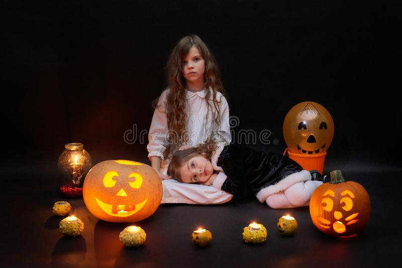 Deux belles filles avec des bougies et des potirons photo stock
