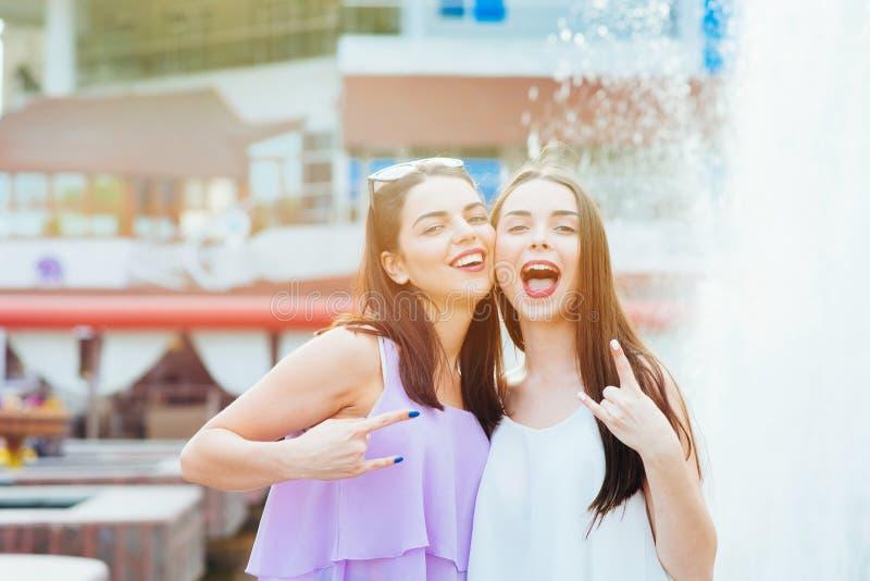 Deux belles filles ayant l'amusement sur la rue image stock