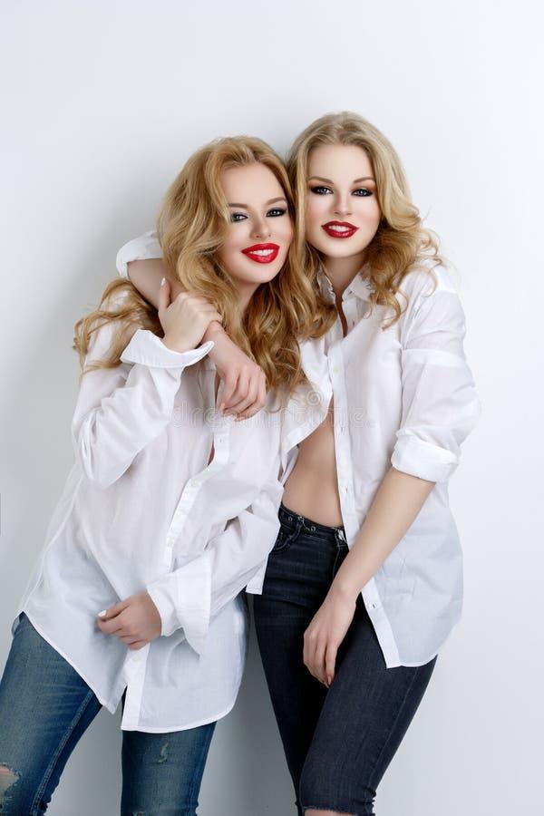 Deux belles filles dans des chemises et des jeans des hommes photos stock