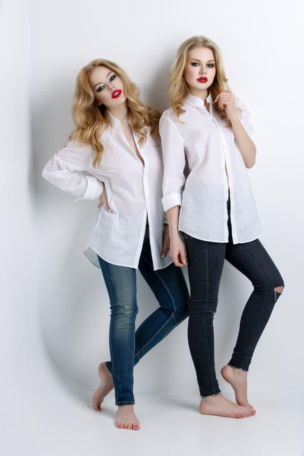 Deux belles filles dans des chemises et des jeans des hommes images stock