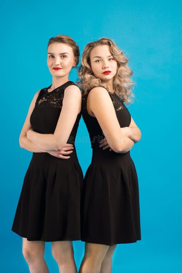 Deux belles filles dans la même robe noire photos libres de droits