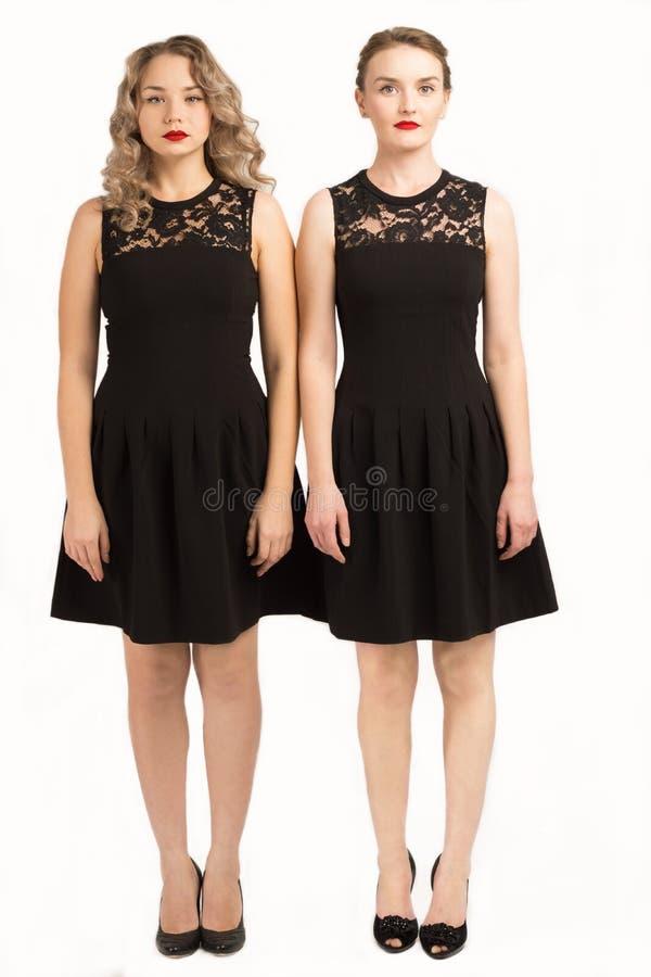 Deux belles filles dans la même robe noire images stock