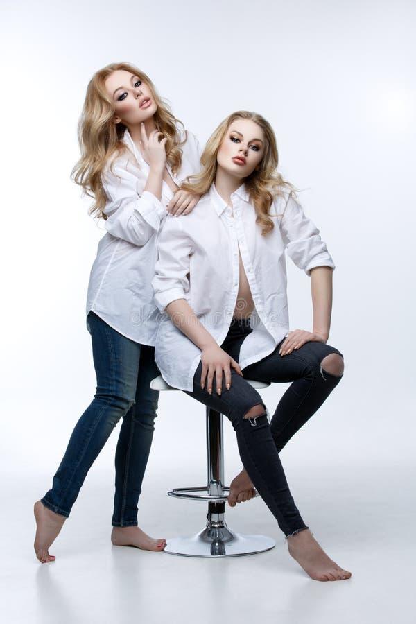 Deux belles filles dans les chemises et des blues-jean blanches photos libres de droits