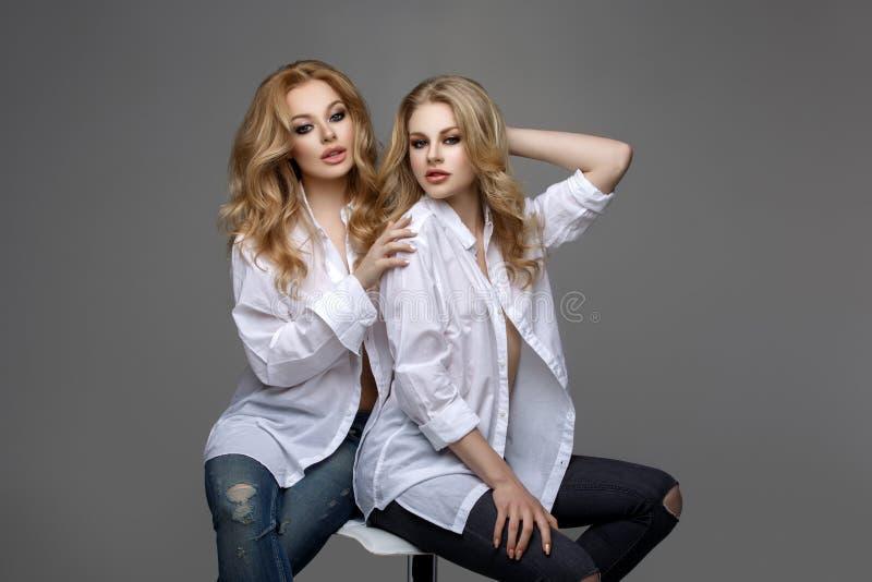 Deux belles filles dans les chemises et des jeans blancs photo libre de droits