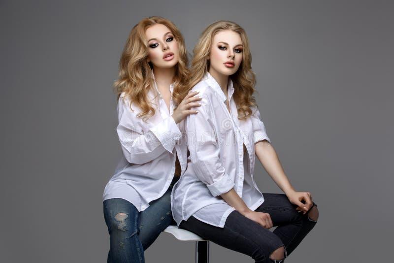 Deux belles filles dans les chemises et des jeans blancs photographie stock