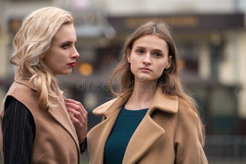 Deux belles filles dans un manteau d'automne images stock