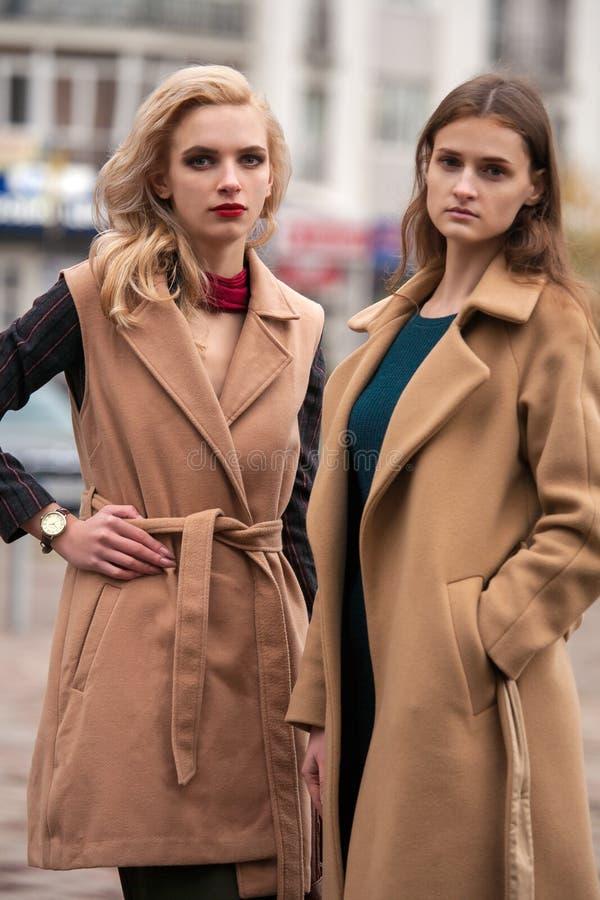 Deux belles filles dans un manteau d'automne images libres de droits