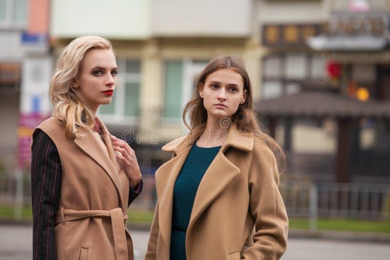 Deux belles filles dans un manteau d'automne photos stock