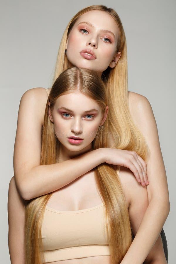 Deux belles filles de jumelles de soeur avec les mêmes longs cheveux blonds et peau parfaite image libre de droits